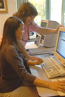 Teacher helping a student at a computer.