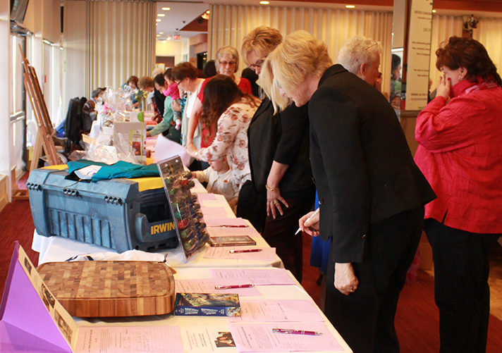 Attendees explore the silent auction on International Women′s Day 2016